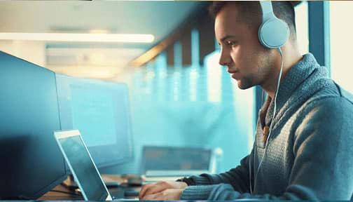 Man wearing headphones working at his laptop