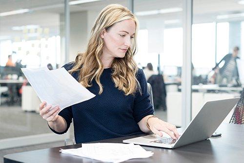 Blonde Frau, die an Laptop arbeitet und ein Blatt Papier in der Hand hält