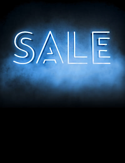 The word SALE illuminated on a dark and misty background