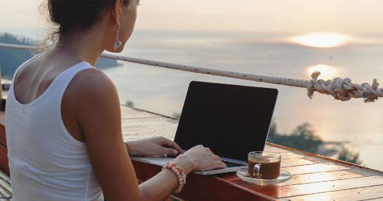 Mujer en un portátil en un entorno mediterráneo