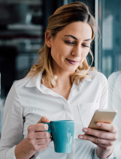 Une femme avec une tasse bleue à la main regarde son smartphone