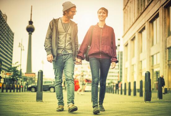 Mann und Frau händchenhaltend vor Stadtkulisse