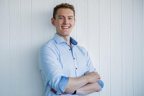 El hombre con camisa azul claro, que cruza los brazos y sonríe en la cámara