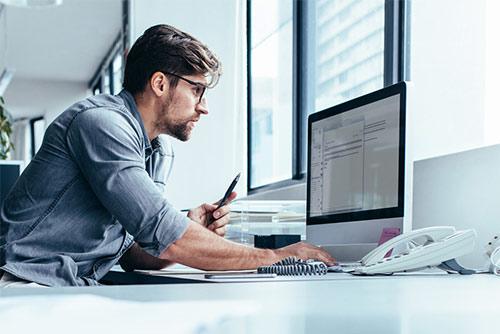 El hombre que trabaja en un ordenador y tiene un bolígrafo en la mano