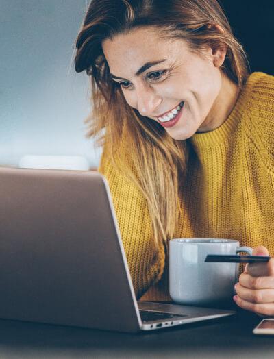 Femme tenant une tasse de café et assise devant un cahier