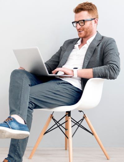 Man on a chair working with his laptop on lis lap
