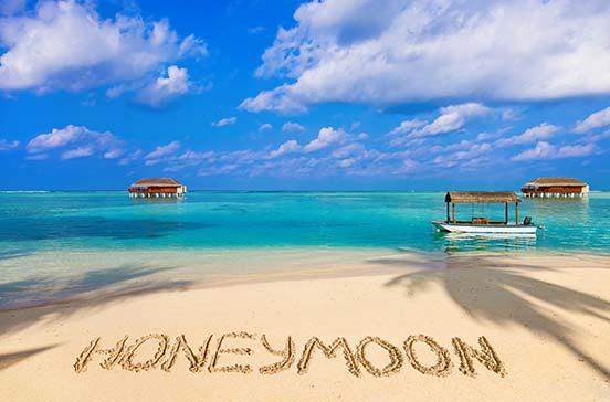 Honeymoon written in the sand on a beach