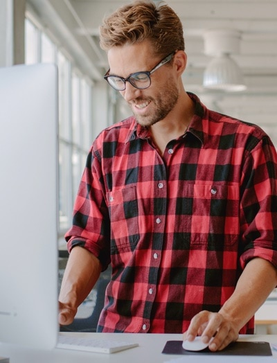 Man in flannel shirt working on his computer, checking his G Suite account