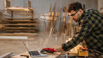 Schreiner arbeitet in seiner Werkstatt am Laptop