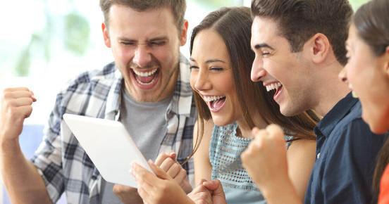 Gruppe von Menschen, die auf ein Tablet schauen und sich freuen