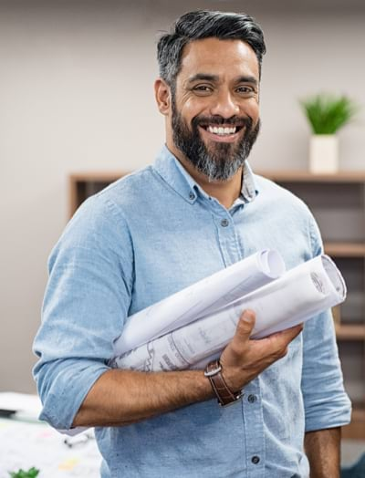 Un homme souriant, avec des plans de construction sous le bras