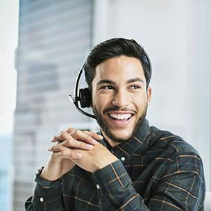 Mann mit Headset, der zur Seite schaut und lächelt