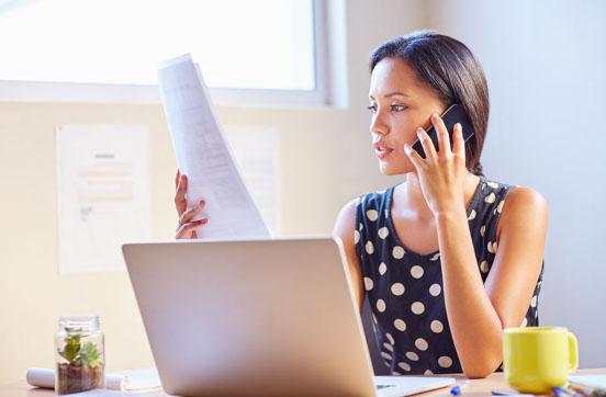 Frau, die telefoniert und auf ein Dokument schaut