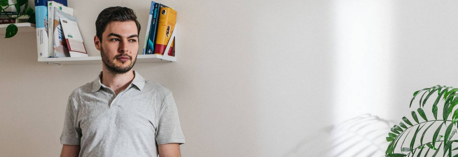 Junger Mann vor Bücherregal