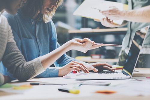 Las personas que trabajan juntas en las computadoras portátiles